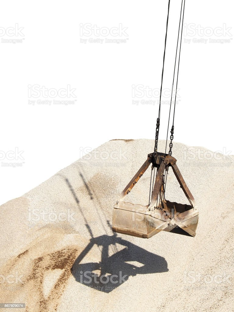 Cargo handling. Industry. Port gantry crane, clamshell bucket on a background of pile of rubble isolated on white background. Grapple cargo crane for bulk freights stock photo