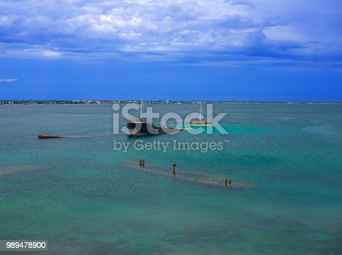 istock Cargo ship and barges stranded near the shore 989478900