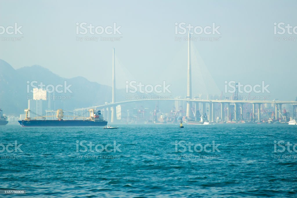 Cargo ship and boats floating in blue sea on car highway background....