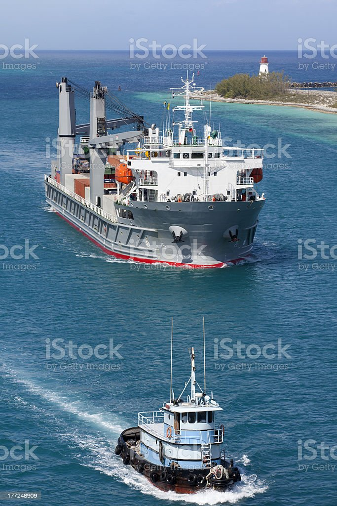 Cargo Ship and Pilot Tug entering harbor with Lighthouse stock photo