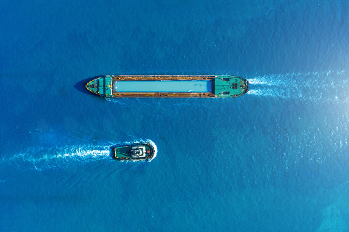 Cargo ship barge and tugboat sail to meet each other in the seaport of the port, aerial view