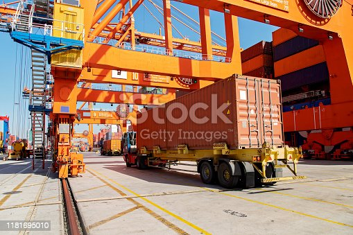 Cargo ship being loaded with containers at port.