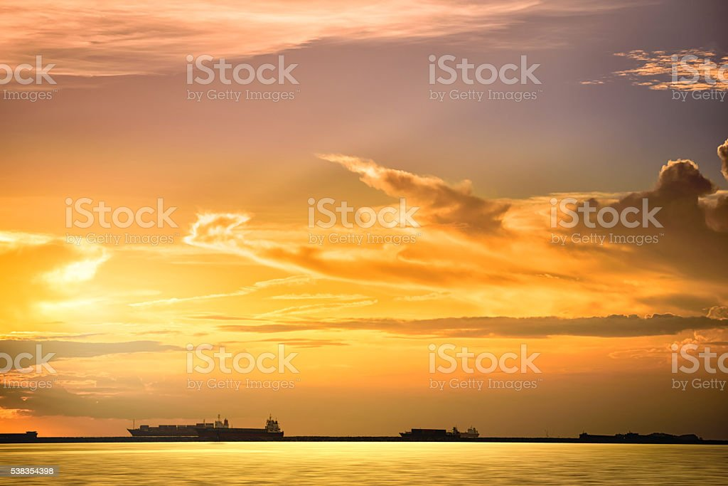Cargo ship floats on the ocean at sunset time. stock photo