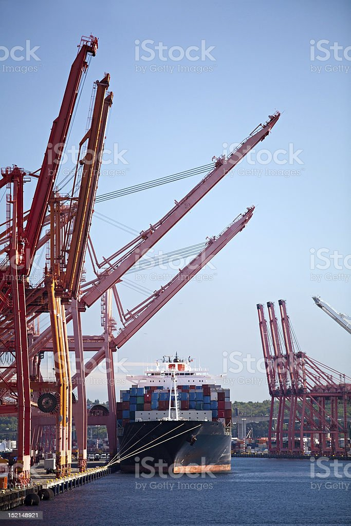 Cargo ship in commercial port with cranes royalty-free stock photo