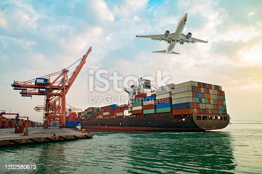 Airplane flying above the container ship. Transportation concept.