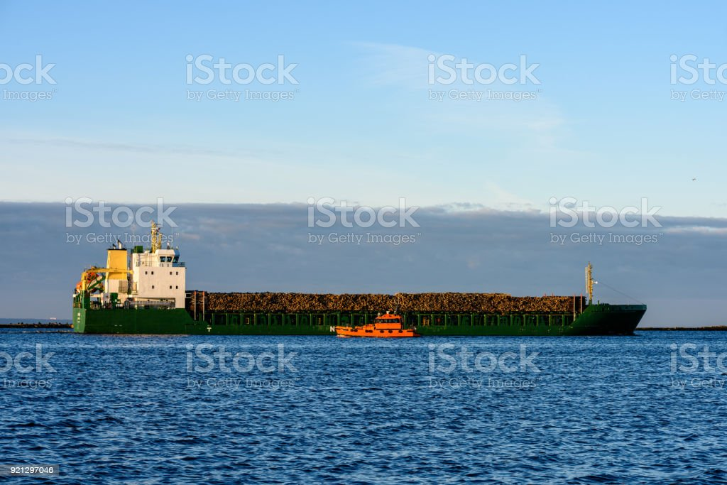 cargo ship is leaving port sailing away stock photo