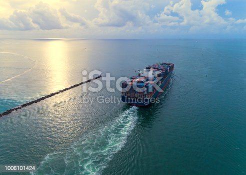 A cargo ship loaded with containers leaves the port of Miami. Aerial View.