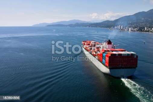 Aerial view of a loaded container ship leaving port.