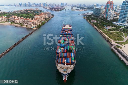 A cargo ship leaves the Port of Miami through the Main Channel. Aerial View.