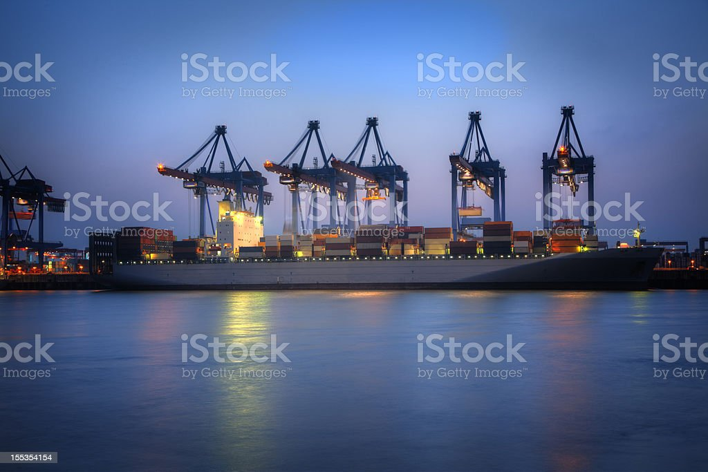 A cargo ship on the sea at sunset royalty-free stock photo