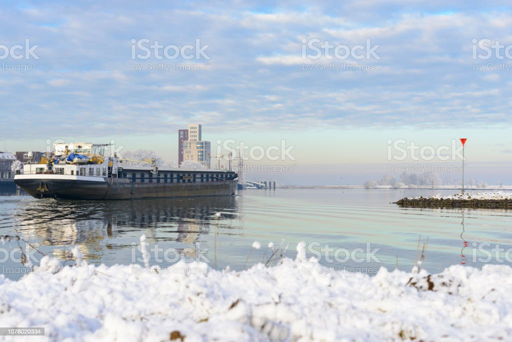 Cargo ship passing through a snowy winter river landscape at the river IJssel stock photo