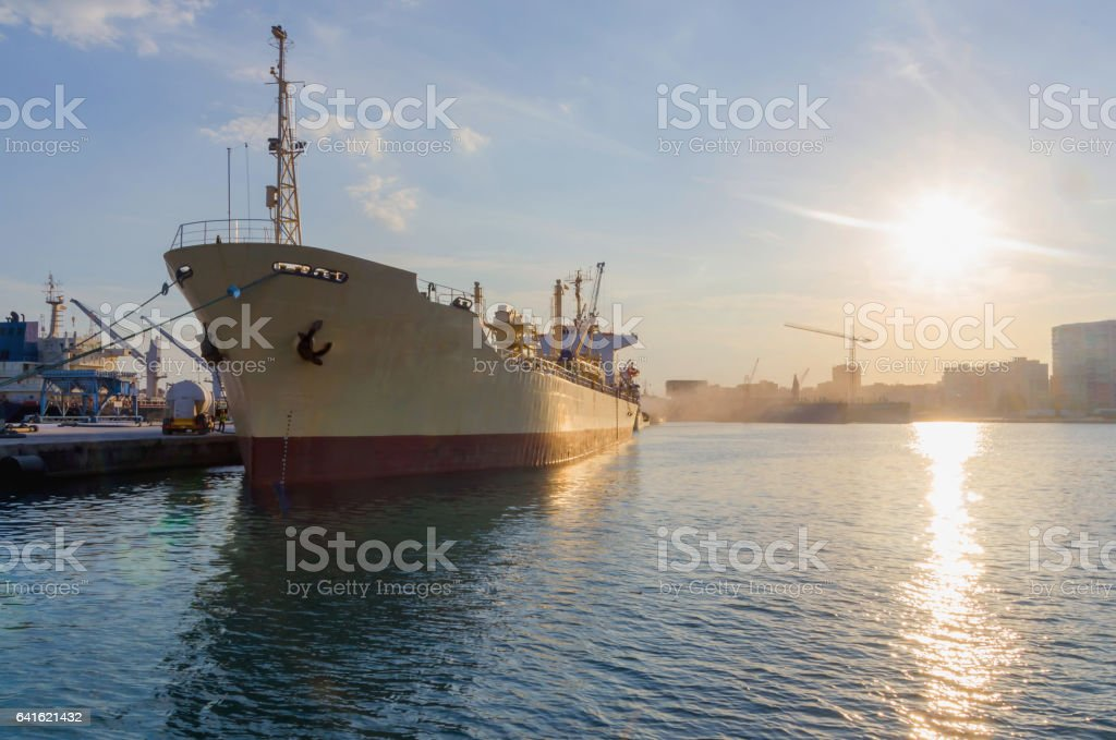 Cargo ship Cargo ship moored in the harbor. Maritime industry transport and logistic concept Anchored Stock Photo