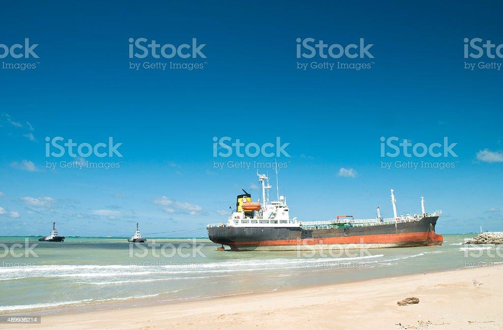 Cargo ship run aground on rocky shore stock photo