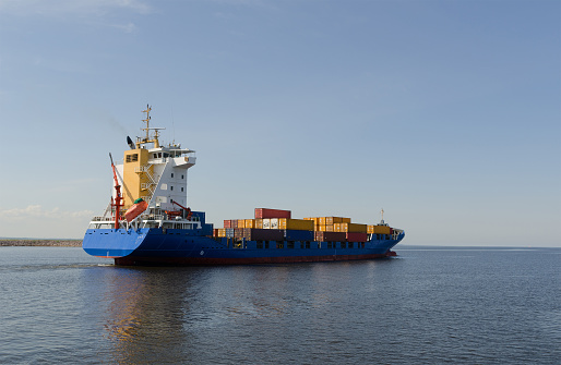 istock Cargo ship sailing in still water 538558662
