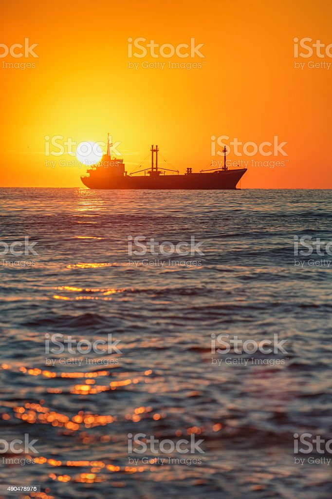 Cargo ship sailing on sunrise near the sea harbor stock photo