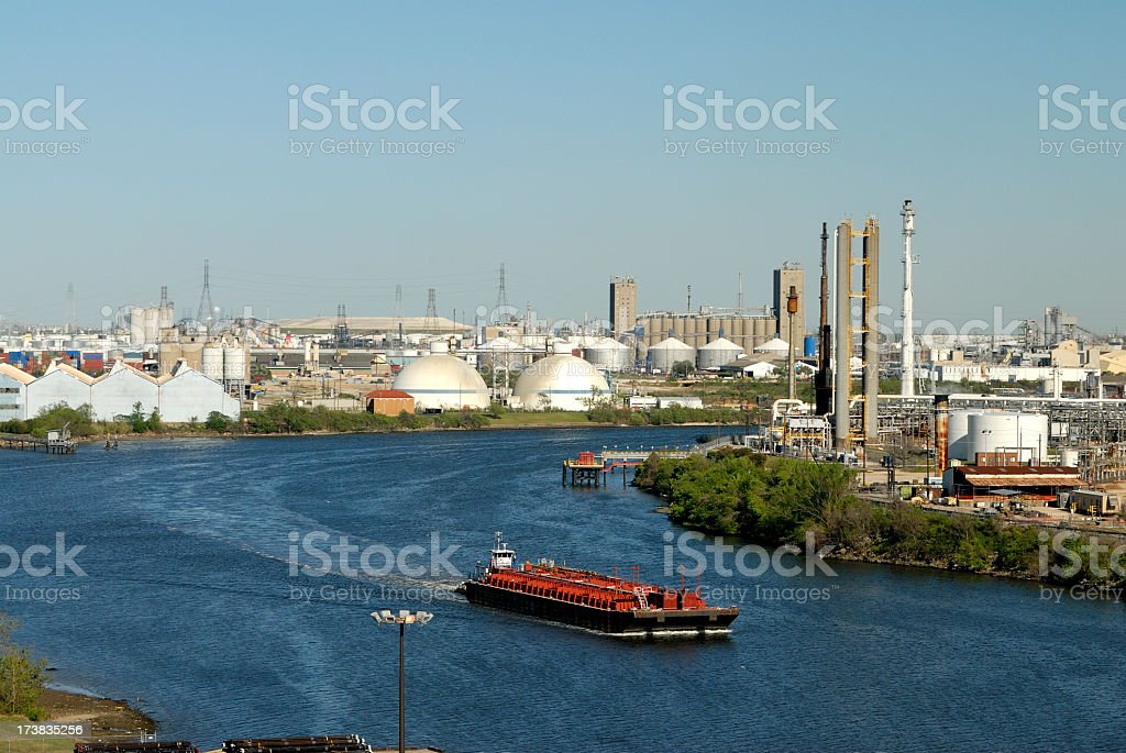A cargo ship sailing out of a city port stock photo