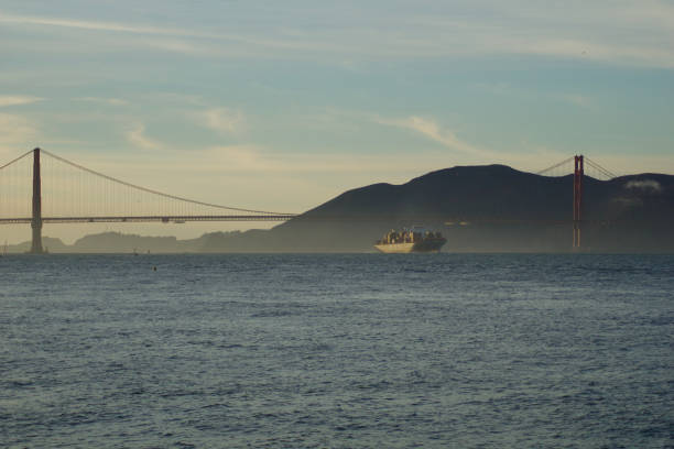 MSC Cargo Ship SILVIA entering the San Francisco Bay under the Golden Gate Bridge on its way to the Port of Oakland - a fully loaded container ship during sunset stock photo