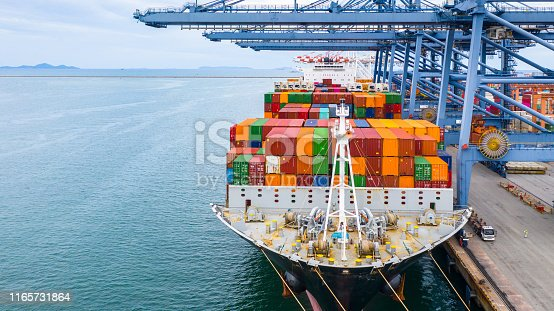 Cargo ship terminal, Unloading crane of cargo ship terminal, Industrial port with containers and container ship.
