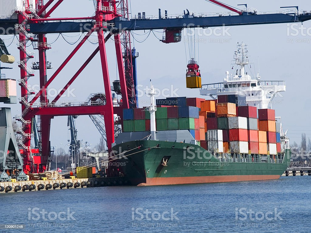 A cargo ship with a container being loaded onto it royalty-free stock photo