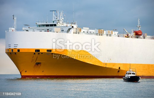 Cargo ship with harbor pilot boat