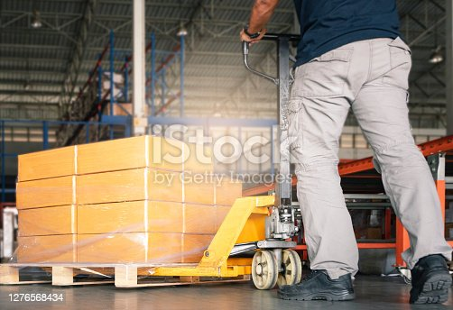 Cargo Shipment, Warehousing, Worker working with hand pallet truck unloading carton product boxes on pallet.