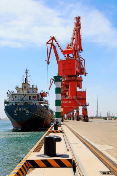 Caofeidian - April 17: Frachtschiffe und Turmdrehkran auf dem Güterbahnhof, am 17. April 2016, Caofeidian, Provinz Hebei, China – Foto