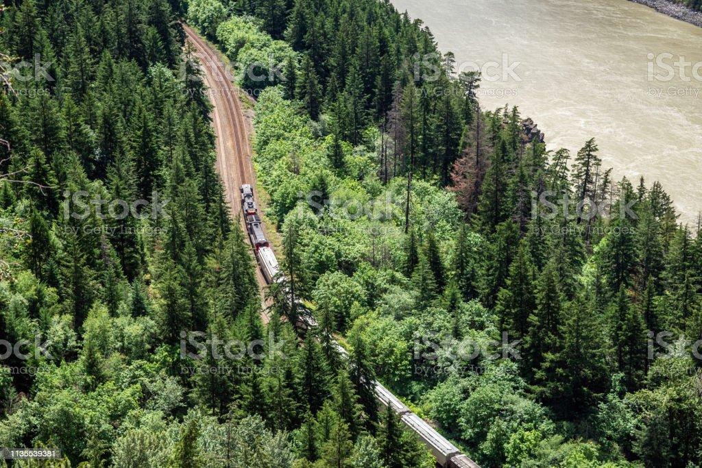 Last tåg på slingrande järnväg linje löper längs en flod - Royaltyfri Behållare Bildbanksbilder