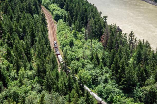 Frachtzug auf der Winding Railroad Line, die entlang eines Flusses verläuft – Foto