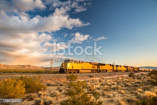 Freight train hauling goods travels on the tracks in the dry California desert