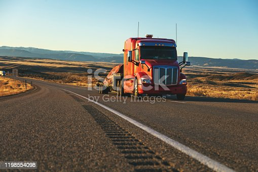Commercial Semi Truck Cargo Transport hauling freight on an Interstate highway in the western USA at dusk during golden hour (Shot with Canon 5DS 50.6mp photos professionally retouched - Lightroom / Photoshop - original size 5792 x 8688 downsampled as needed for clarity and select focus used for dramatic effect)