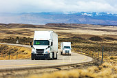 istock Cargo Transport Long Haul Semi Truck On a Rural Western USA Interstate Highway Delivering During Pandemic 1215407298