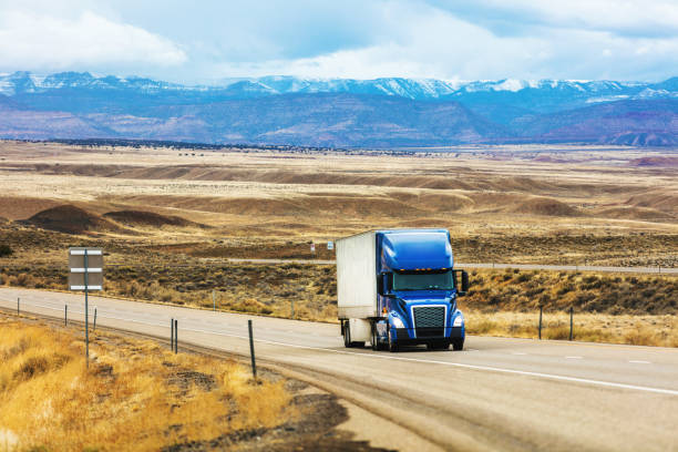 Cargo Transport Long Haul Semi Truck On a Rural Western USA Interstate Highway Delivering During Pandemic stock photo