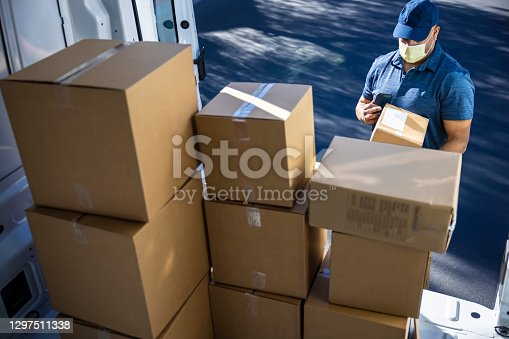 An African American man making deliveries from his cargo van on a sunny day.