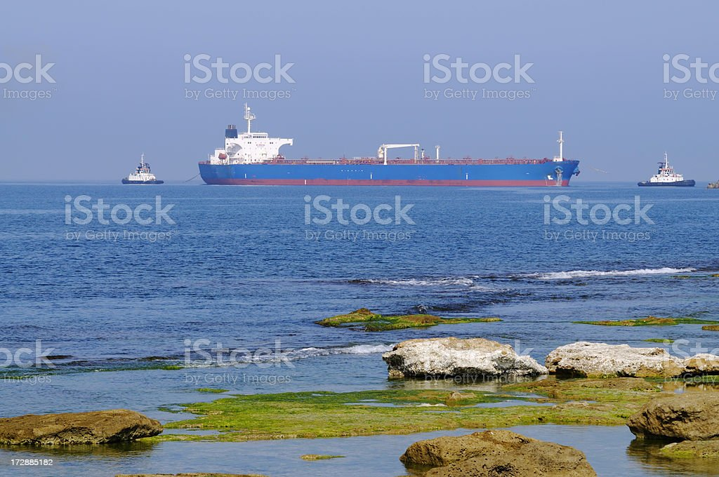 Cargoship with two tugboats royalty-free stock photo