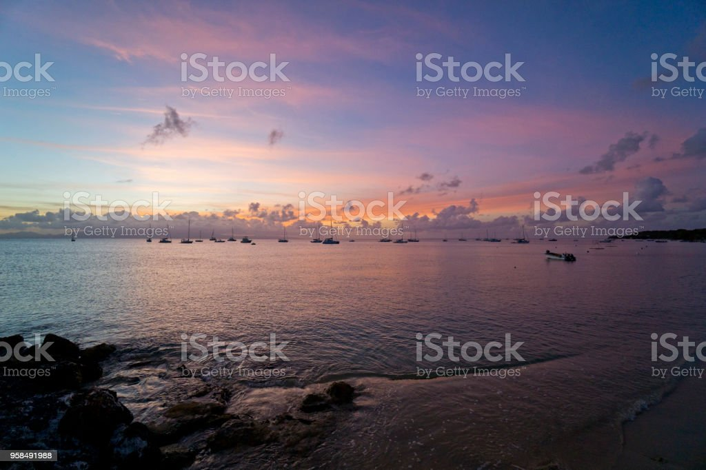 Caribbean, French West Indies, Guadeloupe island, sailing along the coast, view of the sunset over the bay, in the background sailboats and catamarans at anchor. stock photo