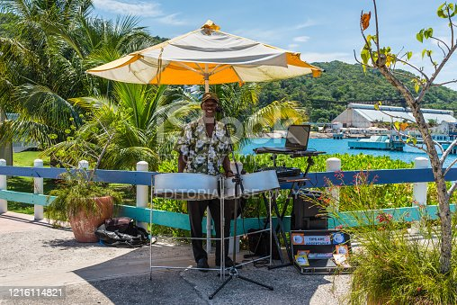 Ocho Rios, Jamaica - April 22, 2019: Local man musician was playing songs on a steel drums near the cruise ship pier in the tropical Caribbean island of Ocho Rios, Jamaica.