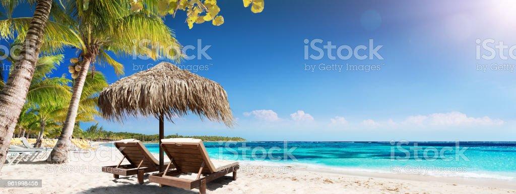 Karibische Palm Beach mit Holzstühlen und Strohschirm - idyllische Insel – Foto