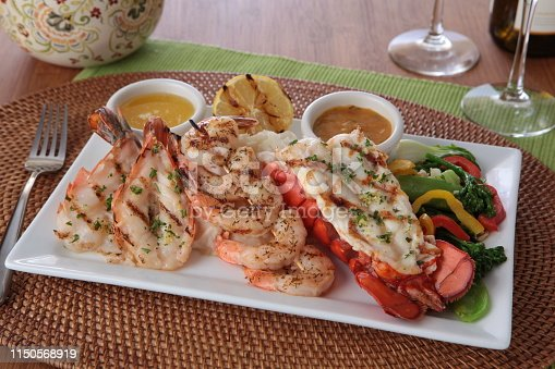 a platter of lobster, shrimp, and roasted vegetables