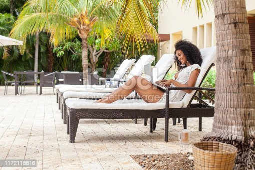 Caribbean woman with dark skin and curly hair of ethnicity between 20-30 years old is working from the laptop in the hotel