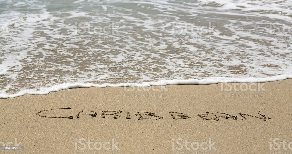 Caribbean written in sand with sea surf royalty-free stock photo