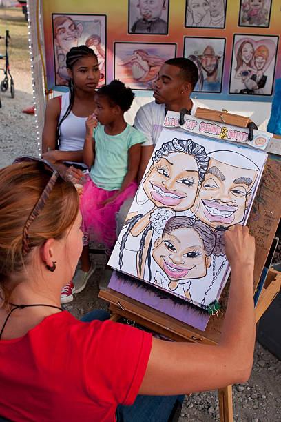 karikatur künstler zieht familien portrait im state fair - karikatur stock-fotos und bilder