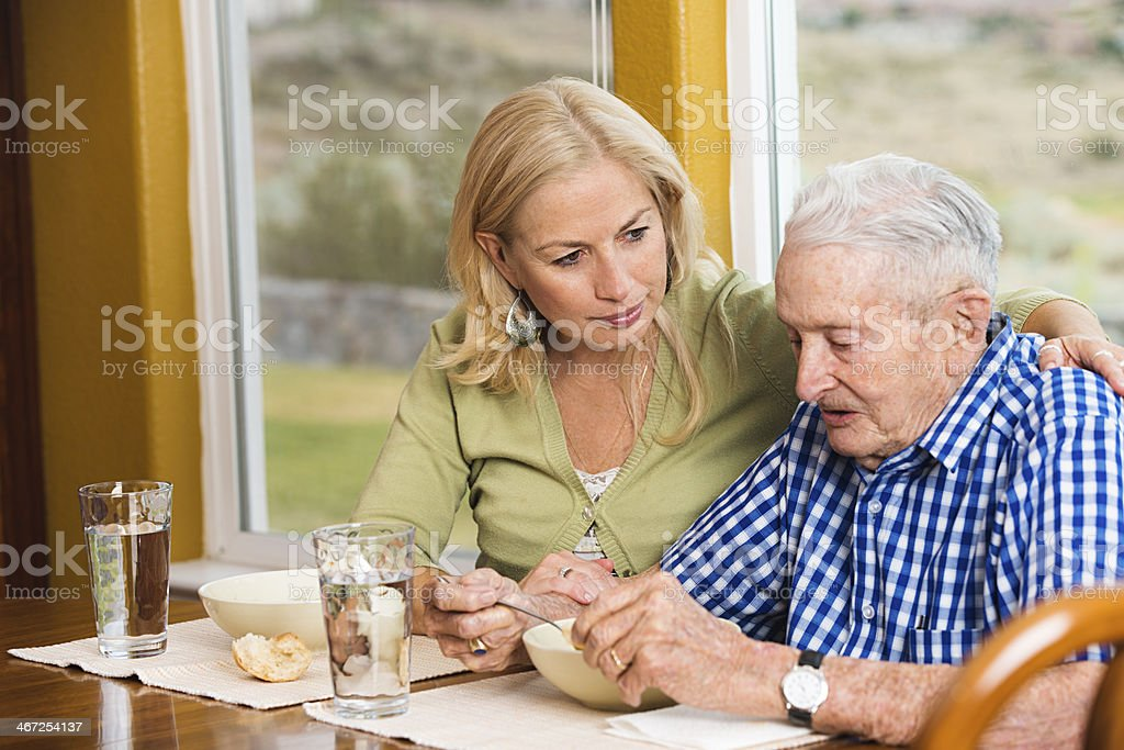 Caring adult daughter watching her senior father eat soup stock photo
