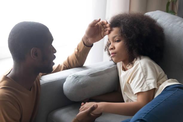 cuidando padre africano tocando la frente de la hija de niño enfermo - enfermedad fotografías e imágenes de stock