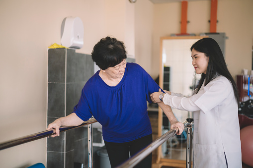 950649706 istock photo Caring asain chinese female physical therapist helps senior woman stroke victim in rehab center walking with the help of parallel bars 1202923478