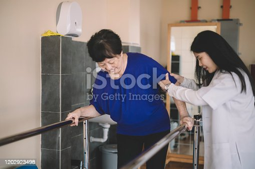 950649706istockphoto Caring asain chinese female physical therapist helps senior woman stroke victim in rehab center walking with the help of parallel bars 1202923498