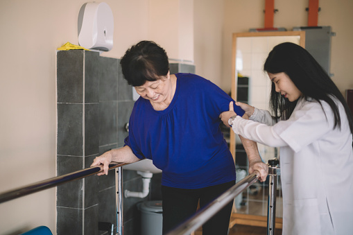 950649706 istock photo Caring asain chinese female physical therapist helps senior woman stroke victim in rehab center walking with the help of parallel bars 1202923498
