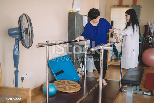 950649706istockphoto Caring asain chinese female physical therapist helps senior woman stroke victim in rehab center walking with the help of parallel bars 1202923668