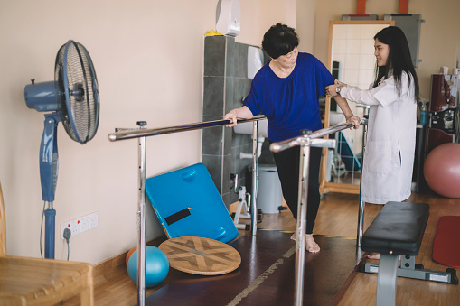 950649706 istock photo Caring asain chinese female physical therapist helps senior woman stroke victim in rehab center walking with the help of parallel bars 1202923668