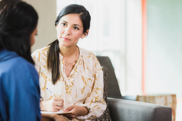 Caring counselor listening to female patient stock photo