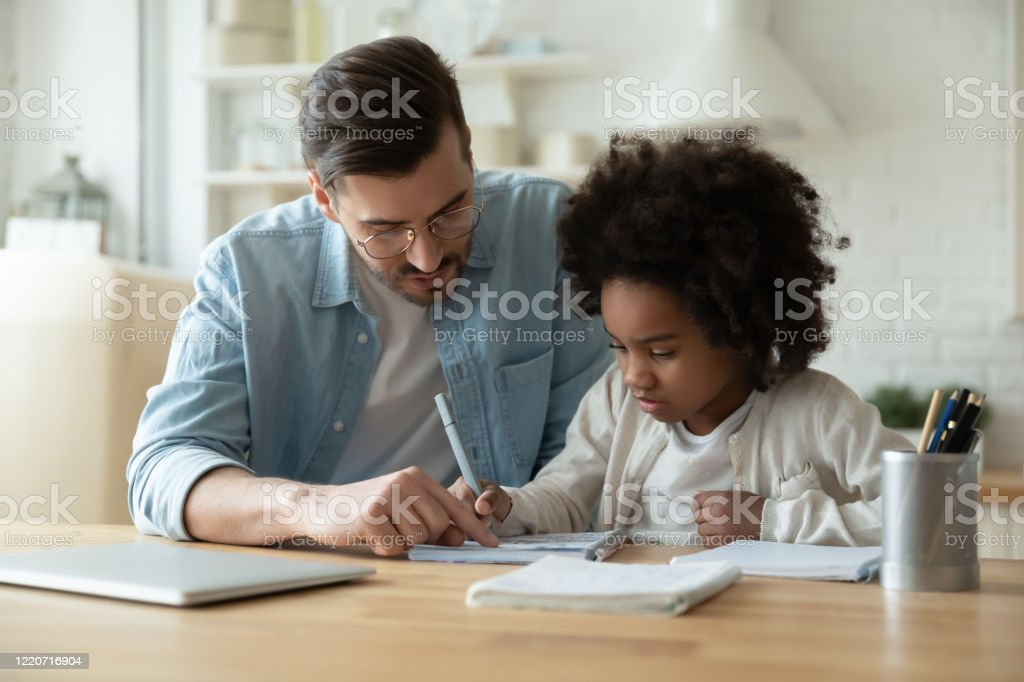 Caring dad help biracial daughter with homework at home Caring Caucasian father help biracial little daughter with homework at home, loving European dad and small African American girl child study together in kitchen on quarantine, homeschooling concept Adoption Stock Photo
